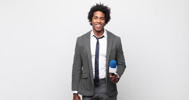 Молодой черный афро-мужчина выглядит счастливым и приятно удивленным, взволнованным, с очарованным и шокированным выражением лица