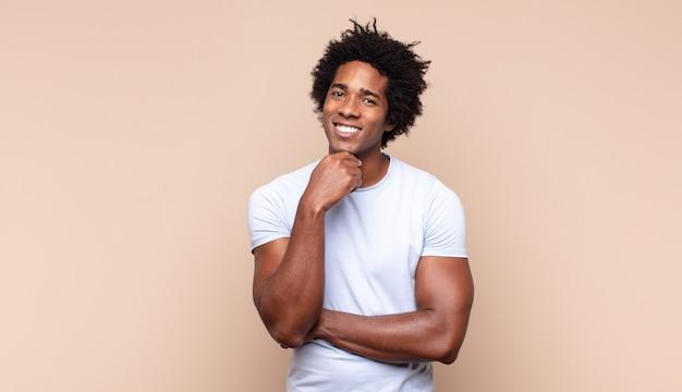 幸せそうに見えて、あごに手を当てて笑って、疑問に思ったり、質問したり、オプションを比較したりする若い黒人のアフロ男