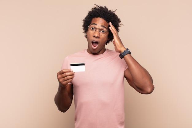 Молодой черный афро-мужчина выглядит счастливым, удивленным и удивленным, улыбается и понимает удивительные и невероятно хорошие новости