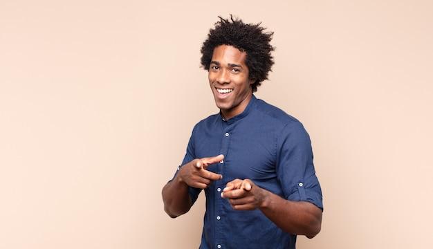 Молодой черный афро-мужчина выглядит гордым, уверенным, крутым, дерзким и высокомерным, улыбается и чувствует себя успешным