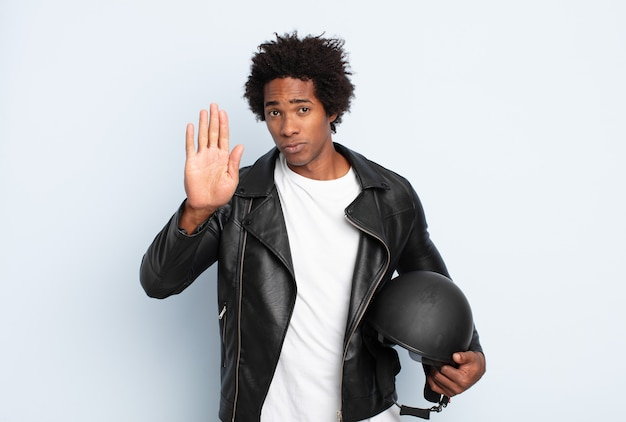 Young black afro man looking serious, stern, displeased and angry showing open palm making stop gesture