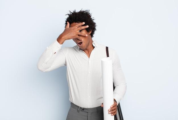 Молодой черный афро-мужчина выглядит шокированным, напуганным или напуганным, закрывает лицо рукой и заглядывает между пальцами