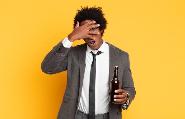 ショックを受けた、怖がった、または恐怖を感じ、手で顔を覆い、指の間をのぞく若い黒人のアフロ男