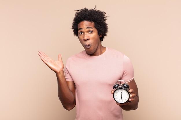Молодой темнокожий афро-мужчина выглядит удивленным и шокированным, с отвисшей челюстью держит объект открытой рукой сбоку