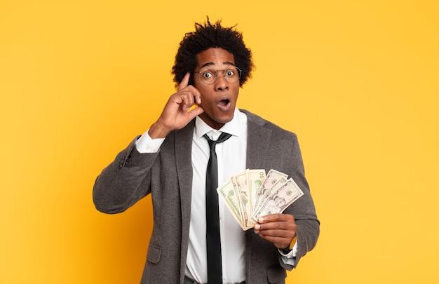 Молодой черный афро-мужчина выглядит удивленным, с открытым ртом, шокированным, осознающим новую мысль, идею или концепцию