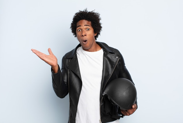 Young black afro man looking surprised and shocked, with jaw dropped holding an object with an open hand on the side