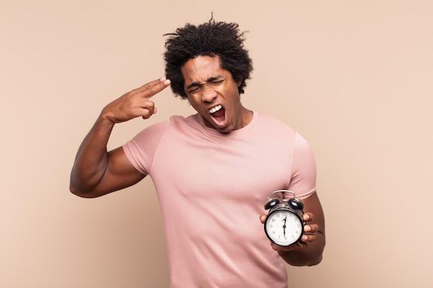 불행하고 스트레스를받는 젊은 흑인 아프리카 남자, 머리를 가리키는 손으로 총 기호를 만드는 자살 제스처