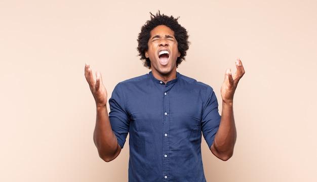 指と怒りの表情でカメラを前に向けて、あなたに義務を果たすように言っている若い黒人のアフロ男