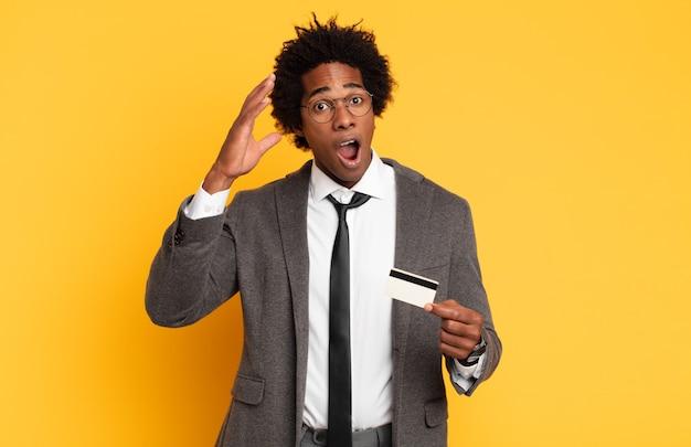 젊은 흑인 아프리카 남자가 공중에서 손으로 비명을 지르며 분노하고 좌절감을 느끼고 스트레스를 받고 화가납니다.