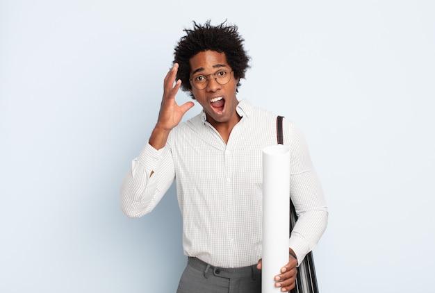 Молодой черный афро-мужчина кричит с поднятыми руками, чувствуя ярость, разочарование, стресс и расстройство