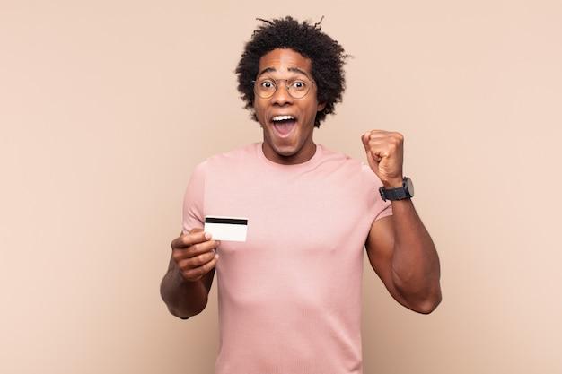 화난 표정으로 또는 주먹으로 공격적으로 외치는 젊은 흑인 아프리카 남자가 성공을 축하합니다.