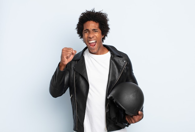 Young black afro man shouting aggressively with an angry expression or with fists clenched celebrating success