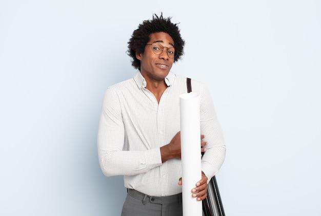 Молодой черный афро-мужчина пожимает плечами, чувствуя смущение и неуверенность, сомневаясь, скрестив руки и озадаченный взгляд