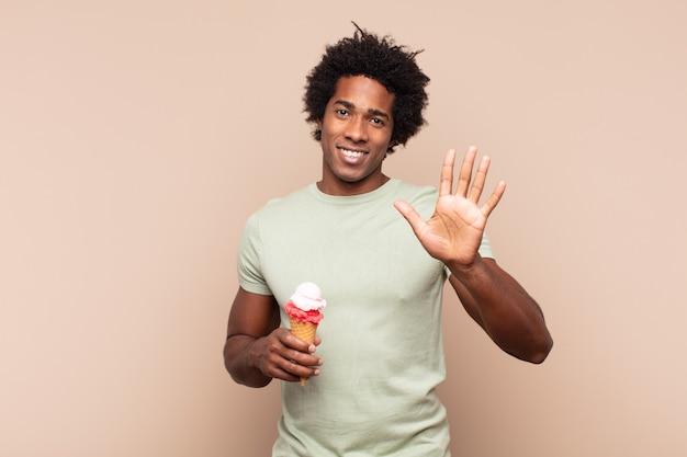 若い黒人のアフロ男が笑顔で親しみやすく、手を前に持って5番か5番を示している