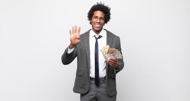 Молодой черный афро-мужчина улыбается и выглядит дружелюбно, показывает номер четыре или четвертый с рукой вперед и считает