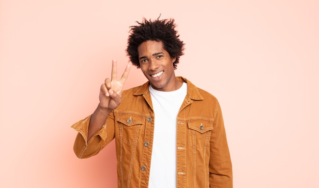 若い黒人のアフロ男は笑顔で幸せそうに見え、のんきで前向きで、片手で勝利または平和を身振りで示す
