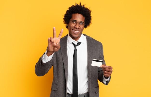 Молодой черный афро-мужчина улыбается и выглядит счастливым, беззаботным и позитивным, жестикулируя победу или мир одной рукой