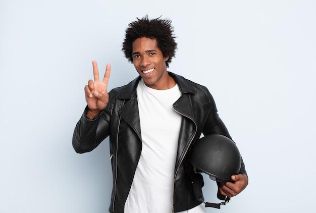 Молодой черный афро-мужчина улыбается и выглядит счастливым, беззаботным и позитивным