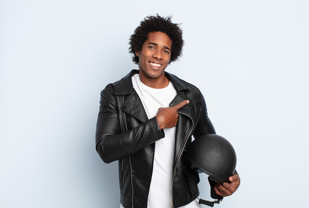 Young black afro man smiling cheerfully, feeling happy and pointing to the side and upwards, showing object in copy space