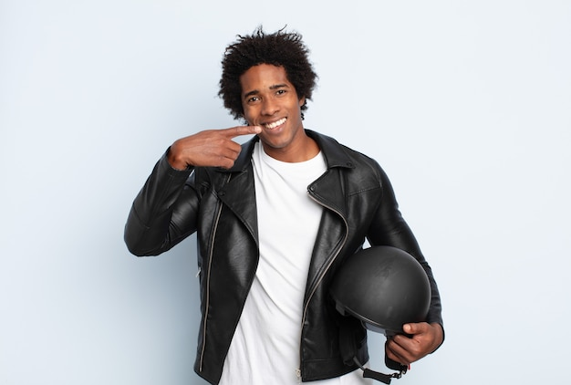Young black afro man smiling confidently pointing to own broad smile, positive, relaxed, satisfied attitude