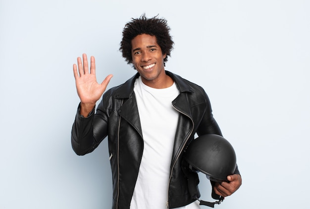 若い黒人のアフロ男が幸せにそして元気に笑って、手を振って、あなたを歓迎して挨拶するか、さようならを言う