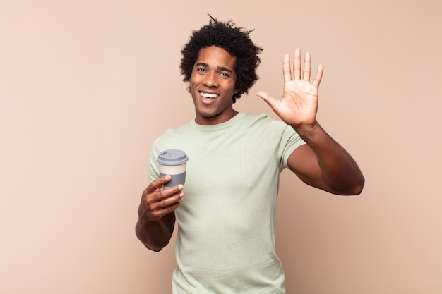 Young black afro man smiling happily and cheerfully, waving hand, welcoming and greeting you, or saying goodbye