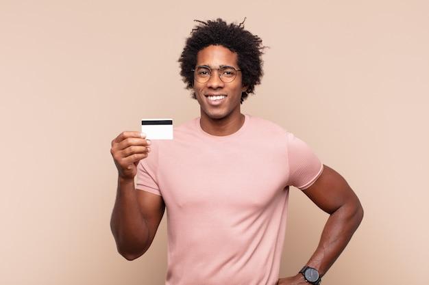 젊은 흑인 아프리카 남자는 엉덩이에 손을 대고 행복하게 웃고 자신감 있고 긍정적이고 자랑스럽고 친절한 태도