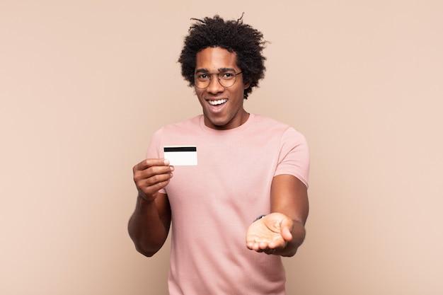 Молодой черный афро-мужчина счастливо улыбается, дружелюбно, уверенно, позитивно смотрит, предлагая и показывая объект или концепцию