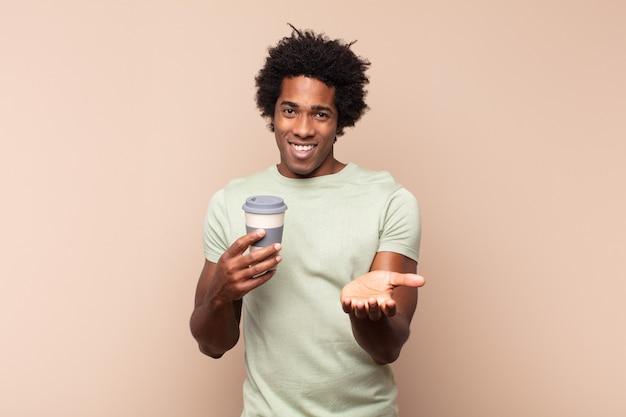 Молодой черный афро-мужчина счастливо улыбается с дружелюбным, уверенным, позитивным взглядом, предлагая и показывая объект или концепцию