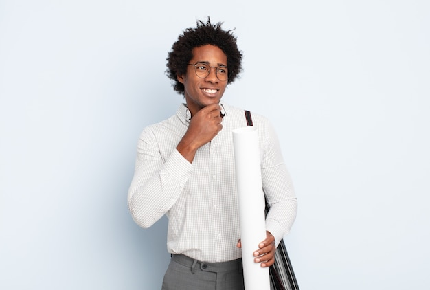 턱에 손으로 행복하고 자신감있는 표정으로 웃고 궁금해하고 측면을 바라 보는 젊은 흑인 아프리카 남자