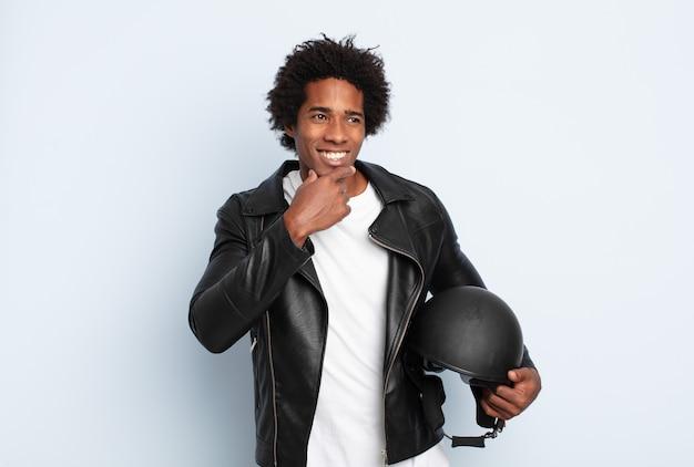 あごに手を添えて幸せで自信に満ちた表情で笑っている若い黒人アフロ男