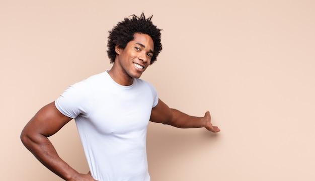 立ってコピースペース、背面図上のオブジェクトを指している若い黒人アフロ男