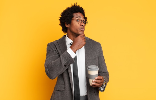 若い黒人のアフロ男は、さまざまな選択肢を持って、疑わしくて混乱していると感じ、どの決定を下すのか疑問に思っています