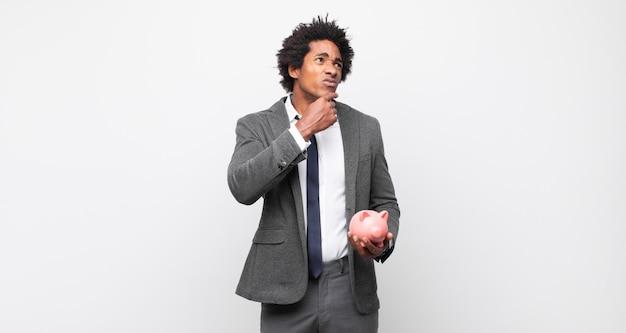 Молодой черный афро-мужчина думает, чувствует себя сомнительным и сбитым с толку, с разными вариантами