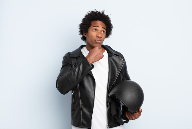 Young black afro man thinking, feeling doubtful and confused, with different options, wondering which decision to make