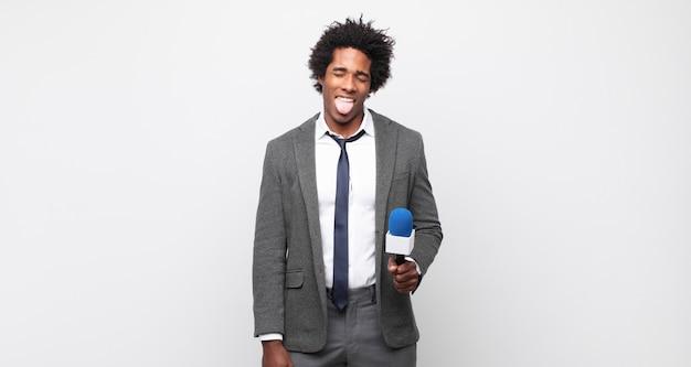 陽気な、のんきな、反抗的な態度、冗談を言って舌を突き出し、楽しんでいる若い黒人のアフロ男