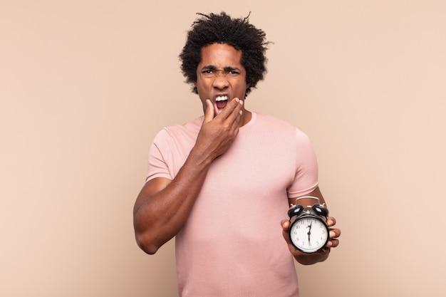 口と目を大きく開いてあごに手を当てている若い黒人のアフロ男は、不快なショックを受けて、何を言っているのか、すごいのか