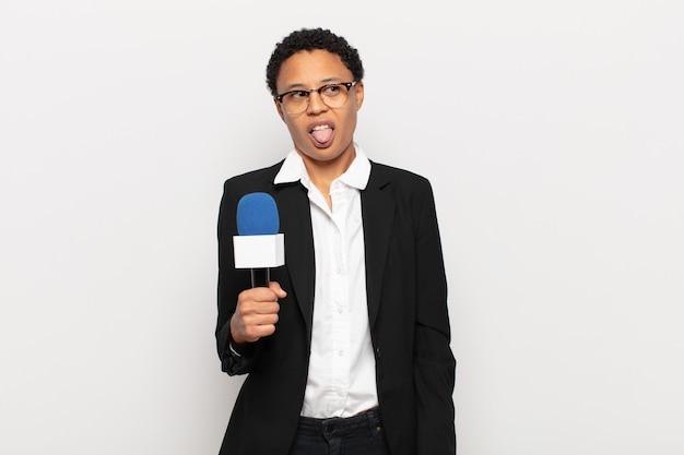 嫌悪感とイライラを感じ、舌を突き出している若い黒人のアフロ女性