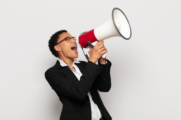 幸せ、興奮、前向きな気持ちで、口の横に手を置いて大きな叫び声を上げ、声をかける若い黒人のアフロ女性