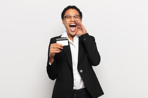 젊은 흑인 아프리카 여성은 행복하고 흥분되며 긍정적인 감정을 느끼며 입 옆에 손을 대고 큰 소리로 외치고 있습니다.