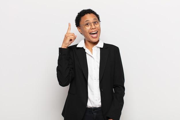 アイデアを実現した後、幸せで興奮した天才のように感じる若い黒人のアフロ女性、元気に指を上げる、エウレカ!