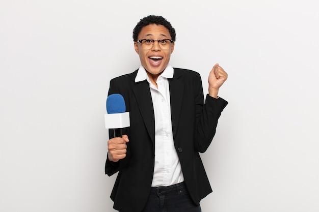Молодая чернокожая афро-женщина чувствует себя потрясенной, взволнованной и счастливой, смеется и празднует успех, говоря