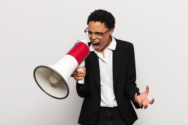 怒っている、イライラしている、欲求不満の叫び声のwtfまたはあなたに何が悪いのかを探している若い黒人のアフロ女性
