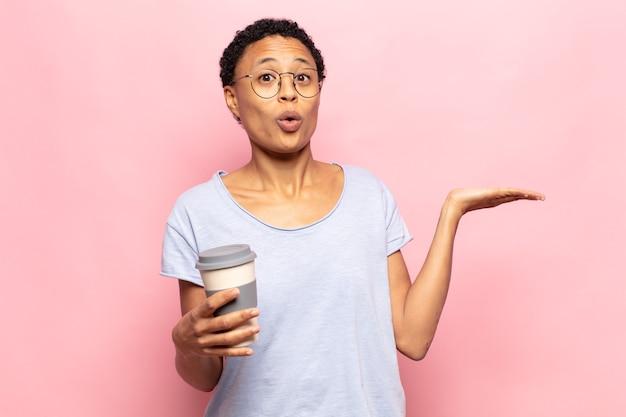 Молодая чернокожая афро-женщина выглядит удивленной и шокированной, с отвисшей челюстью держит объект открытой рукой сбоку