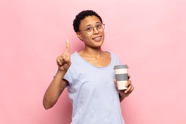 젊은 흑인 아프리카 여자 웃 고 친절 하 게 찾고, 앞으로 손으로 번호 하나 또는 첫 번째 표시, 카운트 다운