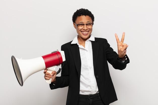 笑顔でフレンドリーに見える若い黒人のアフロ女性、前に手を前に2または2番目を示し、カウントダウン