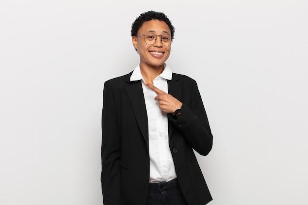 젊은 흑인 아프리카 여자 유쾌하게 웃고, 행복감을 느끼고, 측면과 위쪽을 가리키는, 복사 공간에 물건을 보여주는