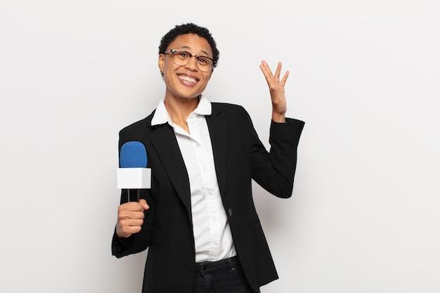 幸せで元気に笑って、手を振って、あなたを歓迎して挨拶するか、さようならを言う若い黒人のアフロ女性