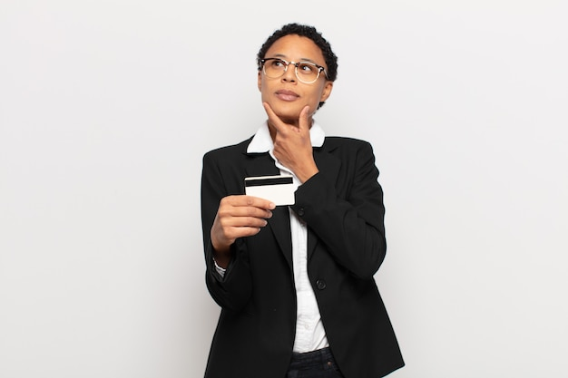 턱에 손으로 행복하고 자신감있는 표정으로 웃고 궁금해하고 측면을 바라 보는 젊은 흑인 아프리카 여성