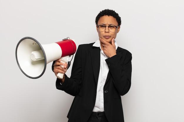 若い黒人のアフロ女性が考え、疑わしくて混乱し、さまざまな選択肢があり、どの決定を下すか疑問に思っています